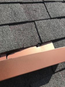aluminum-flashing-sticking-out-from-under-a-roof-shingle